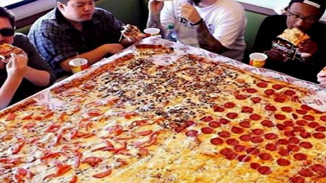 People eating a giant pizza